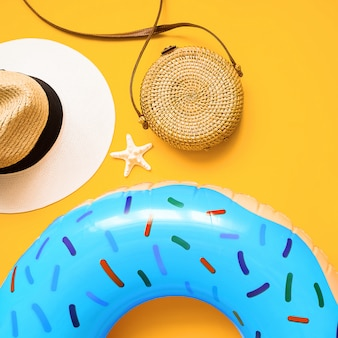 Colorful summer flat lay with blue inflatable circle donut, straw hat, bamboo bag and starfish starfish