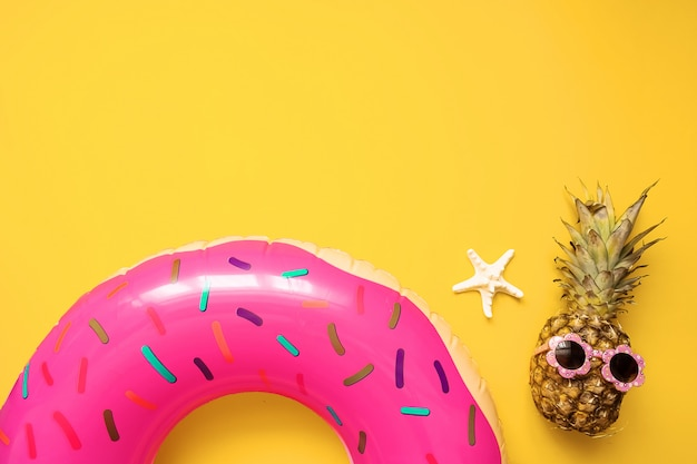 Colorful summer flat lay with pink inflatable circle donut, funny pineapple in sunglasses and starfish starfish