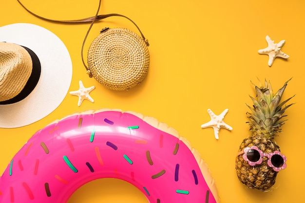 Colorful summer flat lay with pink inflatable circle donut, funny pineapple in sunglasses