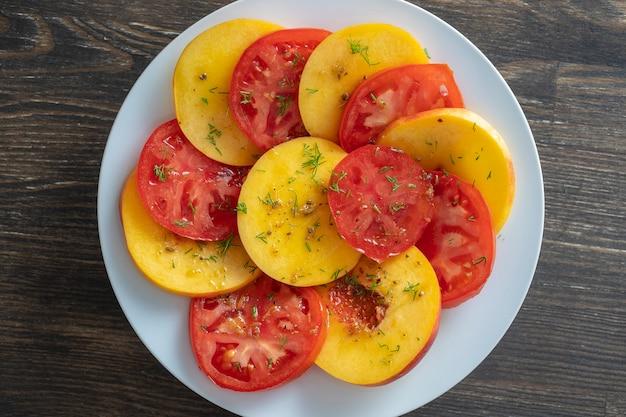 올리브 오일, 레몬 주스, 발사믹 식초 소스로 맛을 낸 토마토와 천도 복숭아를 곁들인 다채로운 여름 샐러드를 닫습니다.