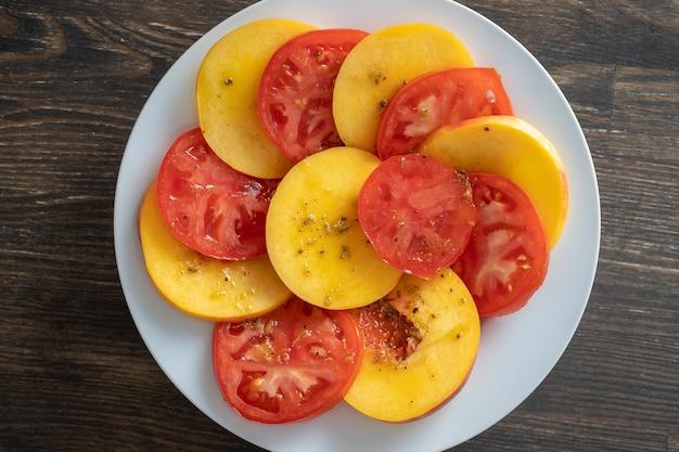 Красочный летний салат с помидорами и нектаринами, заправленный соусом из оливкового масла, лимонного сока и бальзамического уксуса, крупный план