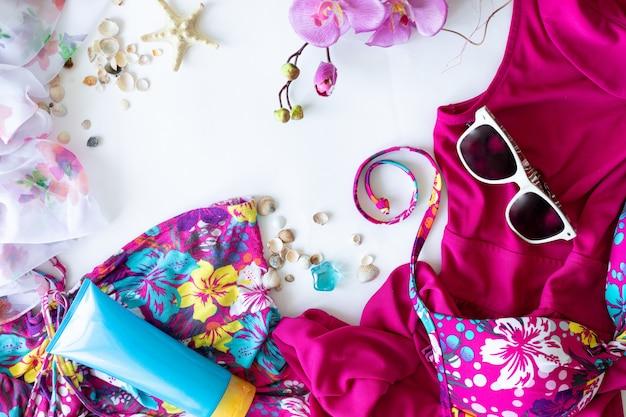 カラフルな夏の女性のファッションフラット服。ドレス、サングラス、化粧品、香水、白い背景の上の花、上面図、幅広い構成。夏のファッション、休暇の概念