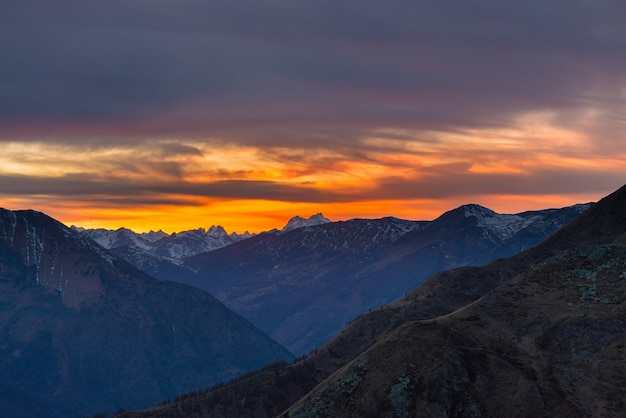 Colorful sunlight behind majestic mountain peaks of the italian french alps