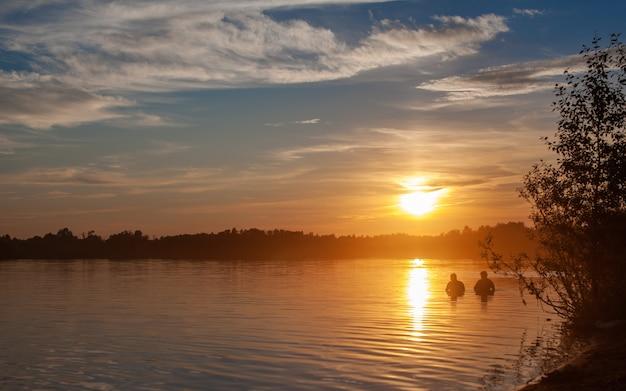 穏やかな湖に沈む夕日。太陽は水面に反射します。