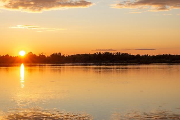 Красочный солнечный закат на спокойном озере. солнце отражается на поверхности воды.