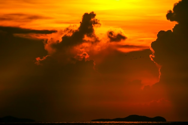 Colorful sunrise on silhouette cloud sky fishing boat and island