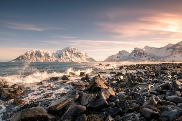Colorful sunrise of snow mountain range with wave hitting on coastline at skagsanden beach