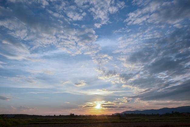 カラフルな夕焼けと日の出と雲。青とオレンジ色の自然。青い空に白い雲がたくさん。今日の天気は晴れ。雲に沈む。空は夕暮れ。