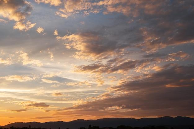 カラフルな夕焼けと日の出と雲。オレンジ色の自然。たくさんの白い雲が空に。今日の天気は晴れ。夕焼けは雲に沈む。空は薄明。