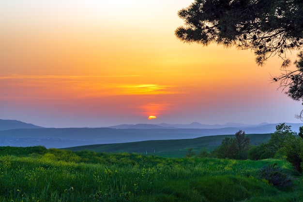 Colorful sunset over green fields