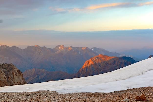 山のカラフルな夕日。山の雪の頂上、ファン、パミール・アライ、タジキスタンの赤い太陽の反射