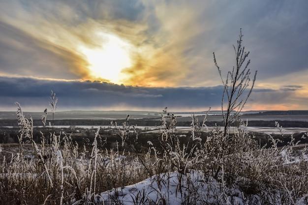 フィールドのカラフルな夕日冬の夕日オレンジ冬のフィールドの明るい夕日カラフルな空