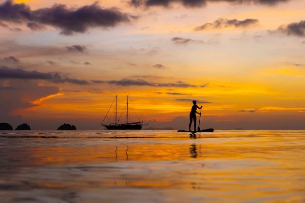 Красочный закат на тропическом пляже. оранжевый закат на берегу океана. красочный закат в тропиках. пара людей плавают на досках