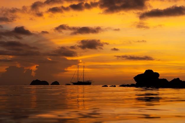 Красочный закат на тропическом пляже. оранжевый закат на берегу океана. красочный закат в тропиках. в воде идет парусный корабль. силуэт парусника с мачтами