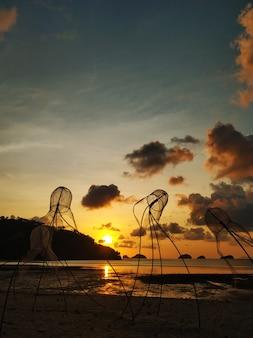 ビーチのカラフルな夕日。水中の夕焼け空の反射。浜辺のクラゲの形の漁網