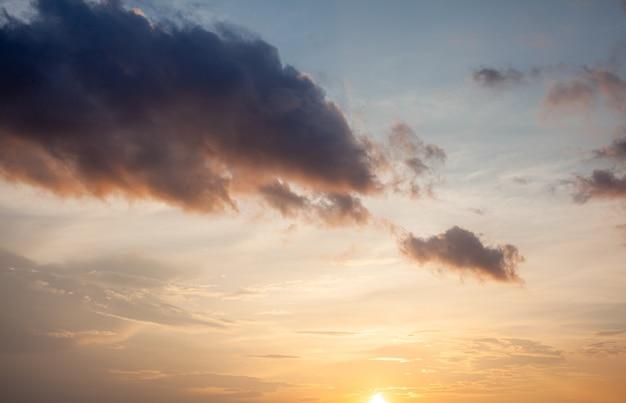 Красочный закат или восход солнца в небе. небо и облака окрашены в разные ярко-оранжевые, желтые и синие цвета.