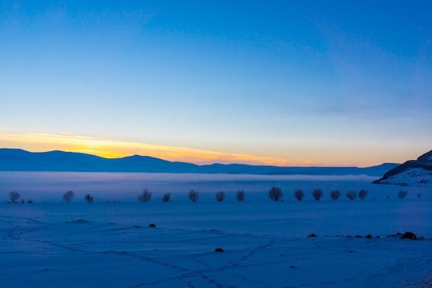 얼어붙은 cildir 호수, kars - 터키 위로 다채로운 일몰