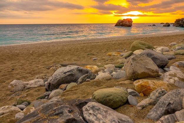 穏やかな海に沈む夕日。石のある粗い砂浜