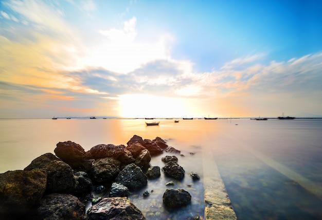 海で岩とカラフルな夕日