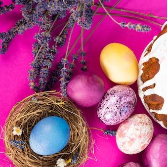 Красочная поверхность с пасхальными яйцами на розовой поверхности