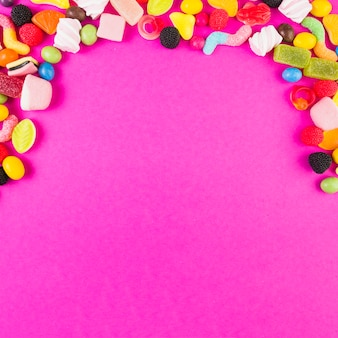 Colorful sweet candies forming arch shape on pink backdrop