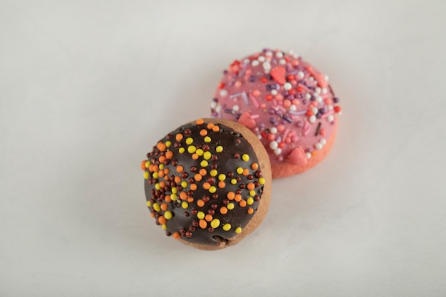 Colorful sweet chocolate small doughnuts with sprinkles .
