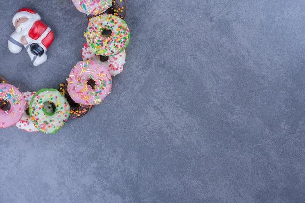 灰色の表面にカラフルな甘い新鮮なドーナツ