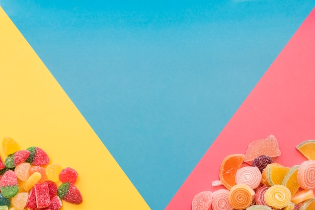 Colorful sweet jelly candies on the yellow and pink triangular background