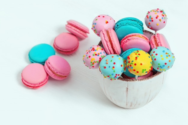 Colorful sweet macaroons and cake pops in bowl on wooden white