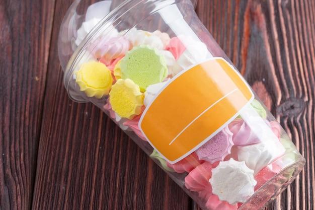 Разноцветное сладкое печенье безе в пластиковом стакане