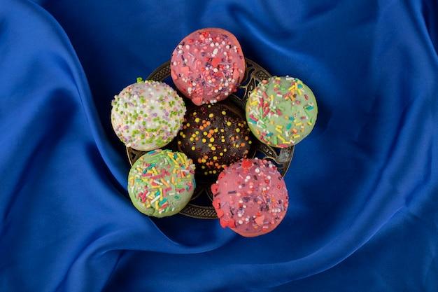 Piccole ciambelle dolci colorate con un pizzico.