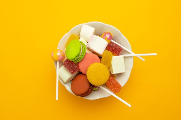 Colorful sweets of sugar candies and marmalade with a white bowl on a bright yellow background
