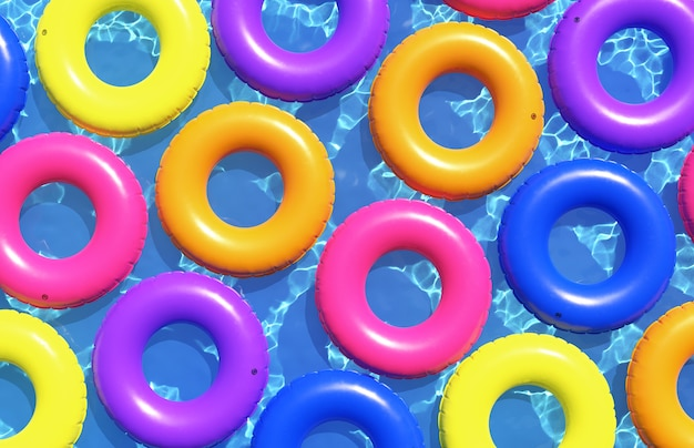 Красочные плавательные кольца на фоне голубой воды