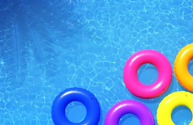 Colorful swimming rings in blue swimming pool, 3d illustration