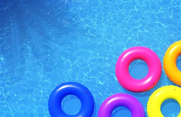 Красочные плавательные кольца в голубом бассейне, 3d иллюстрация