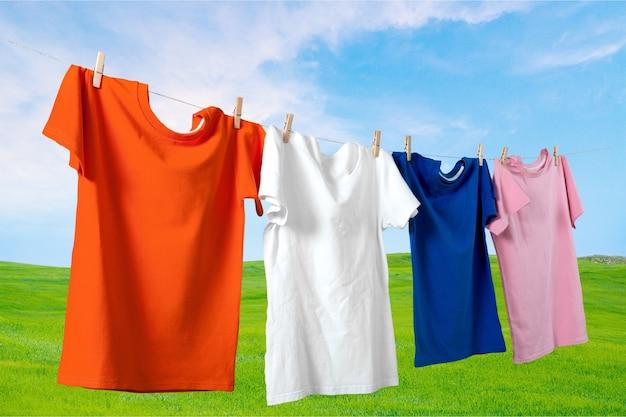 Красочные футболки, висящие на веревке с зеленым полем на фоне