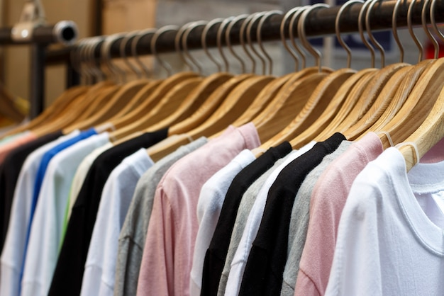 Colorful t-shirts on wooden hangers in store