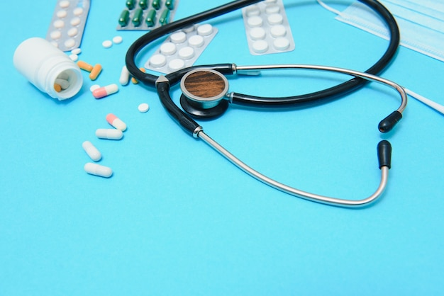 Цветные таблетки и капсулы в коробке, градусник, статоскоп, флакон с антисептиком, емкость, таблетки в упаковке, расположены по периметру изображения на синем фоне.