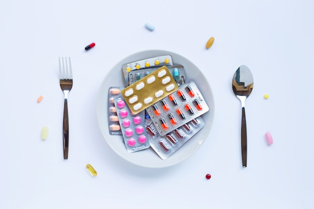 Colorful tablets, capsules and pills with white dish, folk and spoon on white