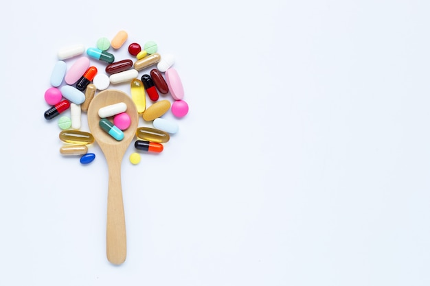 Colorful tablets, capsules and pills with wooden spoon on white