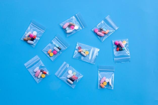 青い表面に薬のプラスチック製のジップロックバッグに入ったカプセルとピルが入ったカラフルなタブレット。上面図