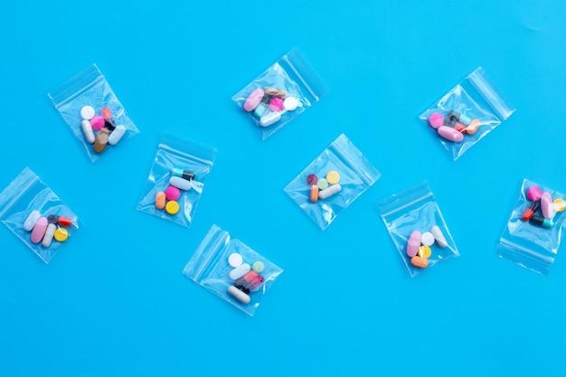 青い壁に薬のプラスチック製のジップロックバッグのカプセルとピルとカラフルなタブレット。上面図