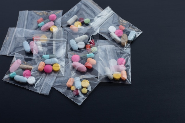 暗い表面の薬のプラスチックジップロックバッグのカプセルと丸薬とカラフルなタブレット。