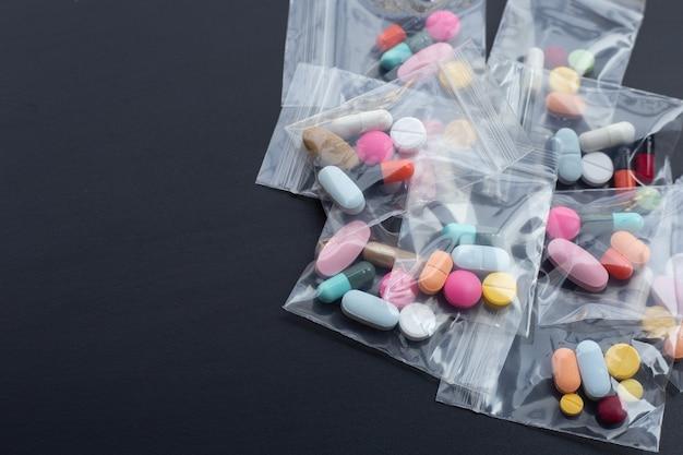 暗い壁に薬のプラスチック製のジップロックバッグにカプセルとピルが入ったカラフルなタブレット。コピースペース