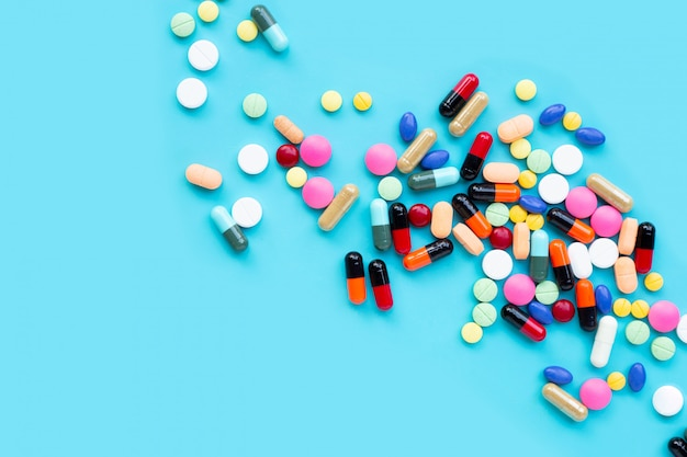 Colorful tablets with capsules and pills on blue