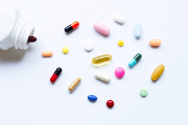 Colorful tablets with capsules and pills on white.