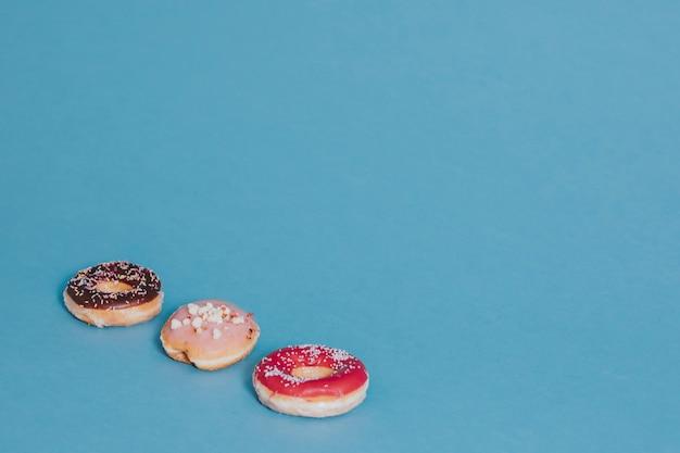 Красочный вкусный глазированный пончик с посыпкой