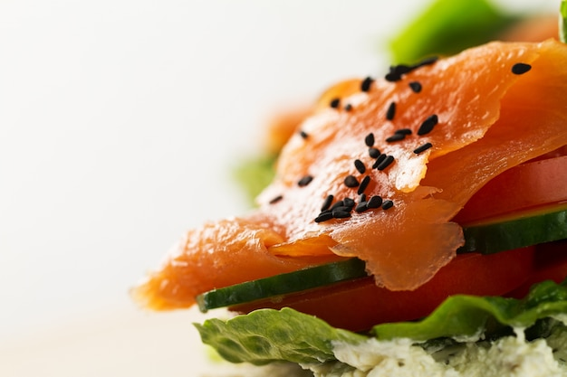 Colorful tasty salted salmon with vegetables on sandwich. bright background. copy space.