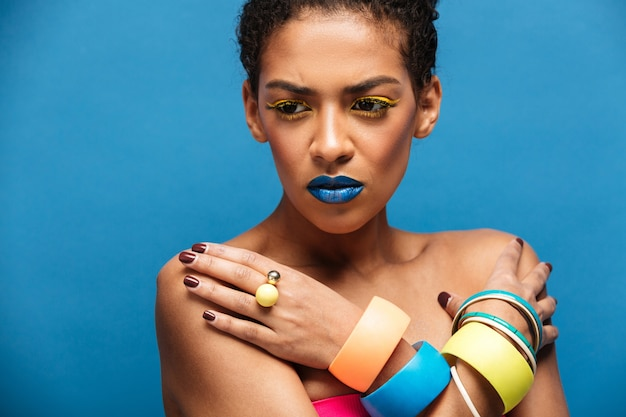 Colorful tense or disappointed mixed-race woman with trendy makeup and accessories posing with crossed hands on chest, over blue wall