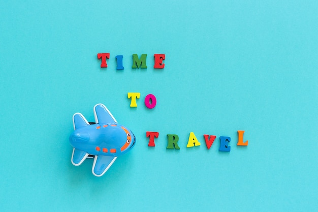 Colorful text time to travel and children's funny toy plane on blue paper background, tourism postcard,